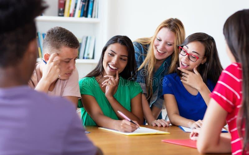 Groep lachende internationale studenten in bespreking stock afbeeldingen