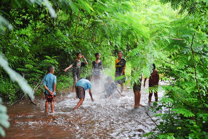 Groep landelijke kinderen die in water samen spelen stock fotografie