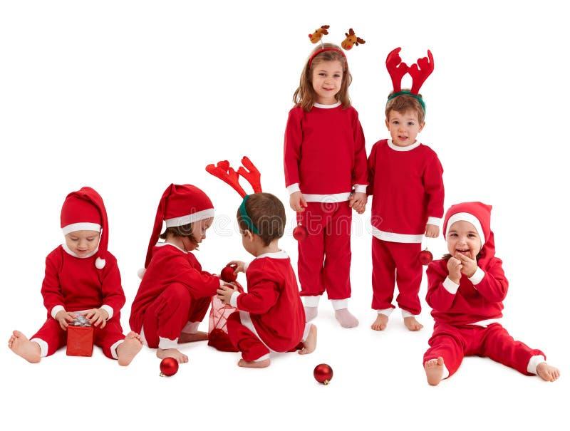 Groep leuke jonge geitjes in Kerstmis het rode kostuum spelen stock afbeelding