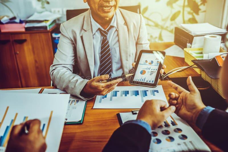 Groep mannelijke ondernemers die beheersproject bespreken tijdens het samenwerken van en het analyseren van boekhoudingshandel en stock afbeeldingen