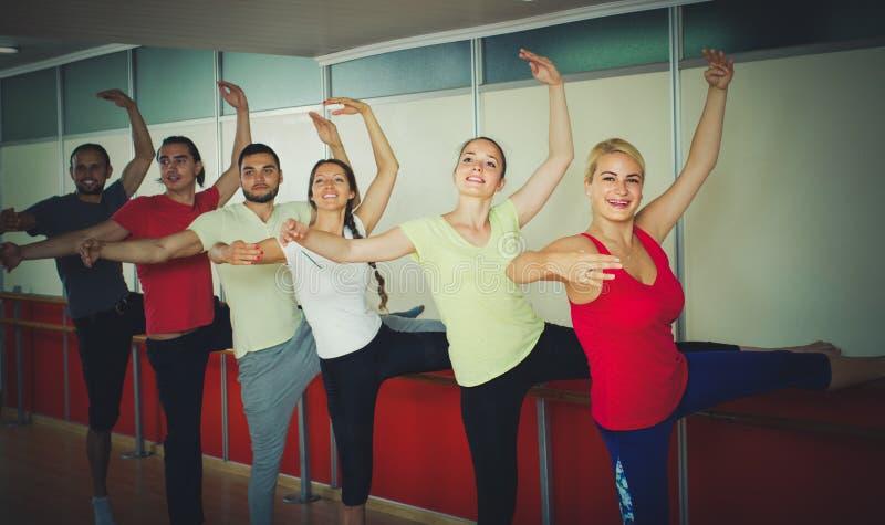 Groep mannen en vrouwen die bij de balletstaaf praktizeren stock afbeelding