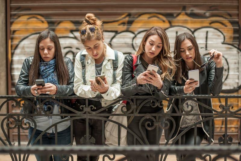 Groep meisjes die cellphones gebruiken Technologieisolatie en emotio stock afbeelding