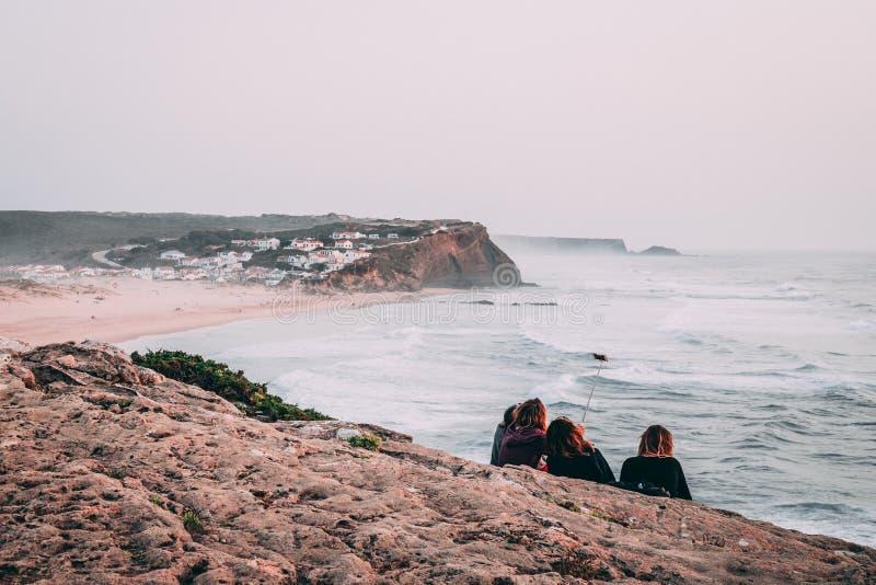 Groep meisjes die op een klip situeren die een selfie met de mening van Monte Clerigo-strand in Portugal nemen stock fotografie