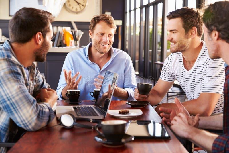 Groep mensen die bij een koffiewinkel spreken stock fotografie