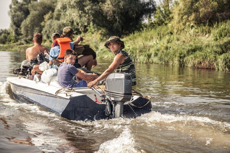 Groep mensen die op motorboot door rivier aan het de jachtkamp tijdens jachtseizoen varen stock fotografie