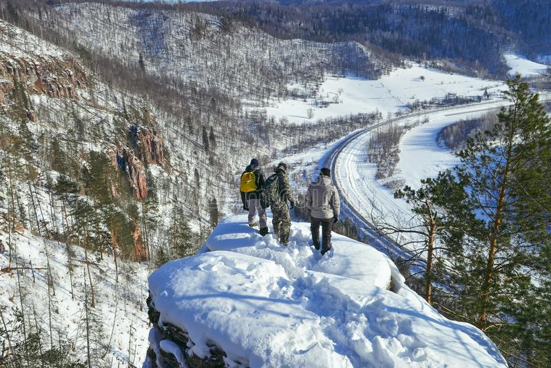 Groep mensen die zich bij bergpiek bevinden en neer van hoge hoogte zonnige de winterdag bekijken stock fotografie