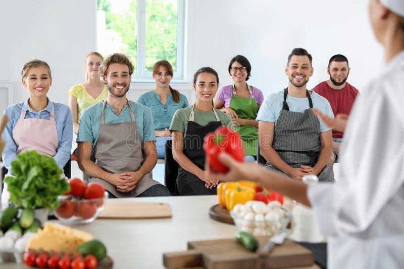 Groep mensen en vrouwelijke chef-kok stock afbeelding