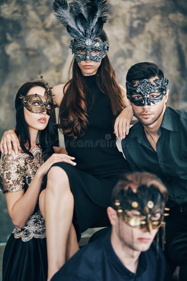 Groep mensen in het masker van maskeradecarnaval het stellen in studio royalty-vrije stock afbeelding