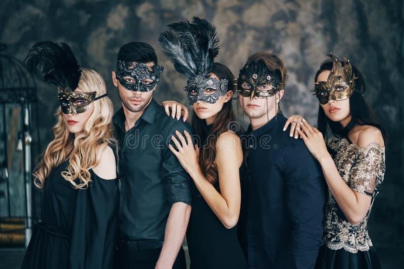 Groep mensen in het masker van maskeradecarnaval het stellen in studio stock foto's