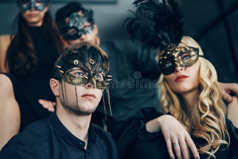 Groep mensen in het masker van maskeradecarnaval het stellen in studio stock afbeeldingen