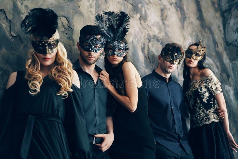 Groep mensen in het masker van maskeradecarnaval het stellen in studio royalty-vrije stock fotografie