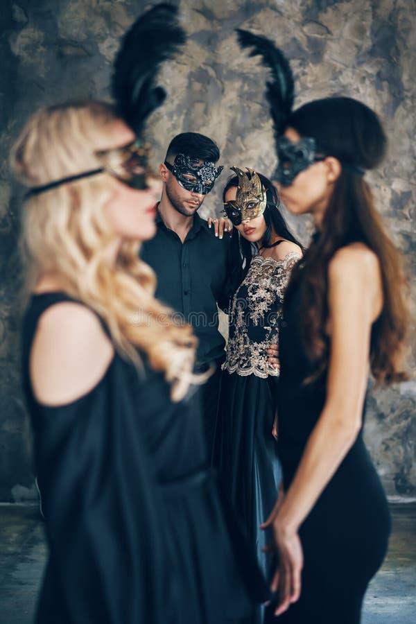 Groep mensen in het masker van maskeradecarnaval het stellen in studio royalty-vrije stock foto