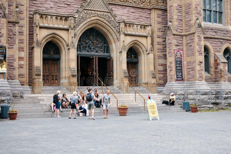 Groep mensen op de ingangsladders de zitten van St James United Protestant kerk en open de kerk die ondertekenen met een lgbtrege stock afbeelding