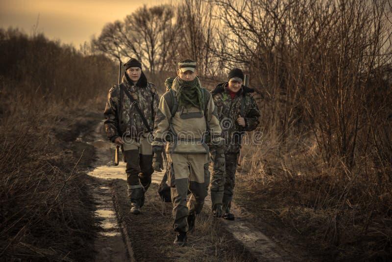 Groep mensenjagers met de jachtmateriaal die op de landelijke zonsondergang van het weg jachtseizoen gaan stock afbeelding