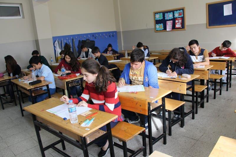 Groep middelbare schoolstudenten die een test in klaslokaal nemen stock afbeeldingen