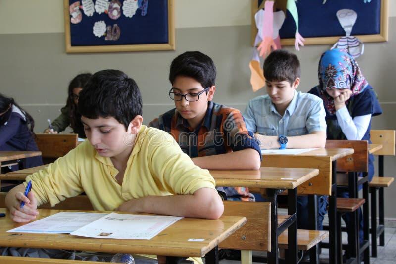 Groep middelbare schoolstudenten die een test in klaslokaal nemen stock foto