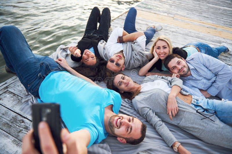 Groep mooie jongeren die Selfies liggend op de pijler, de beste vrienden van meisjes en jongens met genoegen doen stock foto's