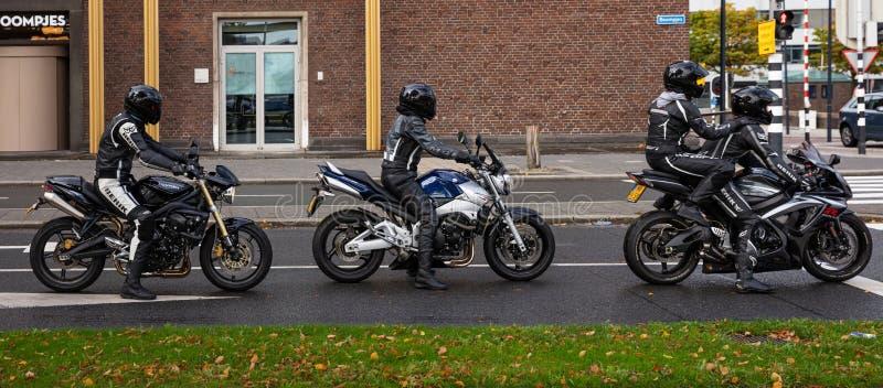 Groep motorrijders in lederkleding en helmen die wachten op het groene licht banner stock foto