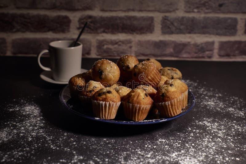 Groep muffins naast een kop van melk stock foto