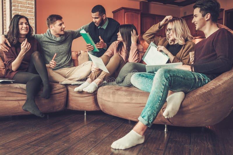 Groep multi etnische jonge studenten die voor examens in huisbinnenland voorbereidingen treffen royalty-vrije stock afbeelding