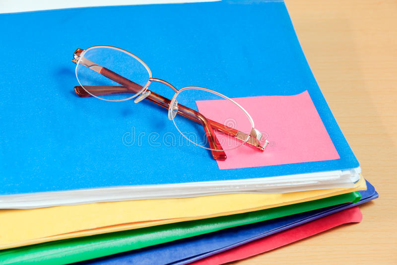 Groep multicolored bureauomslagen en glazen stock foto's