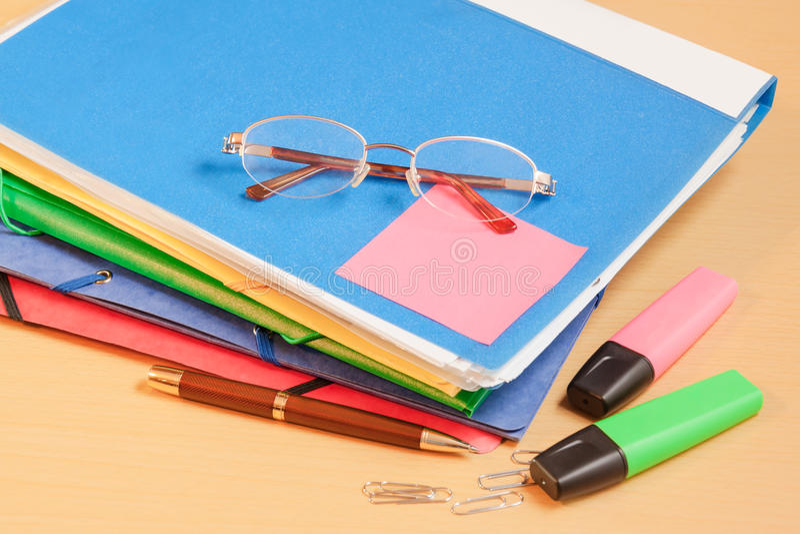 Groep multicolored bureauomslagen, glazen en bureau supplie stock afbeelding