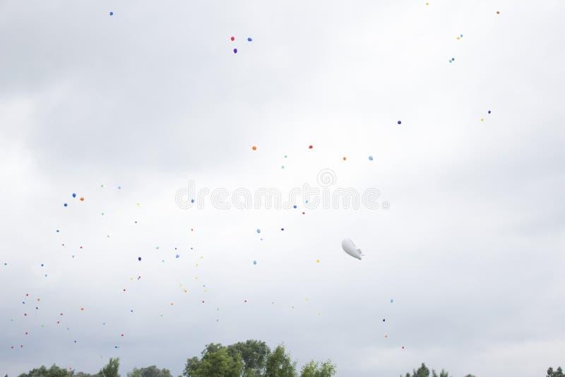 Groep multicolored helium gevulde ballons in de hemel stock fotografie