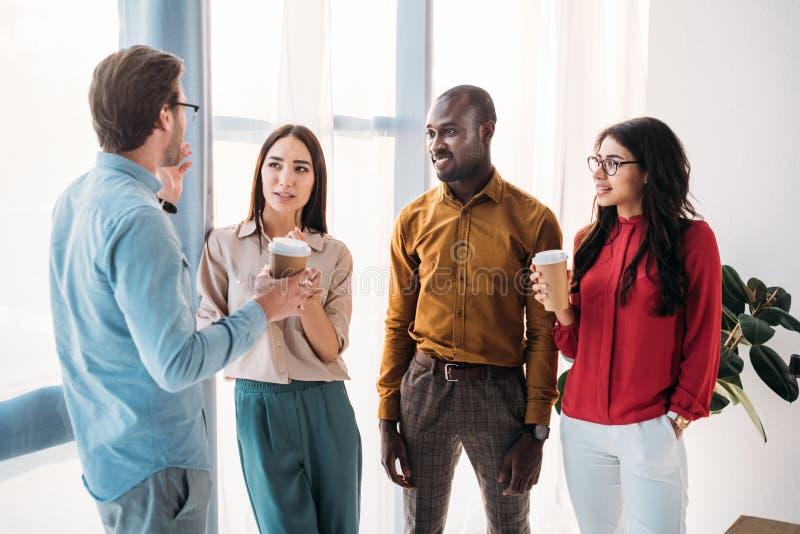 groep multiculturele bedrijfsmensen die gesprek hebben tijdens koffiepauze royalty-vrije stock afbeeldingen