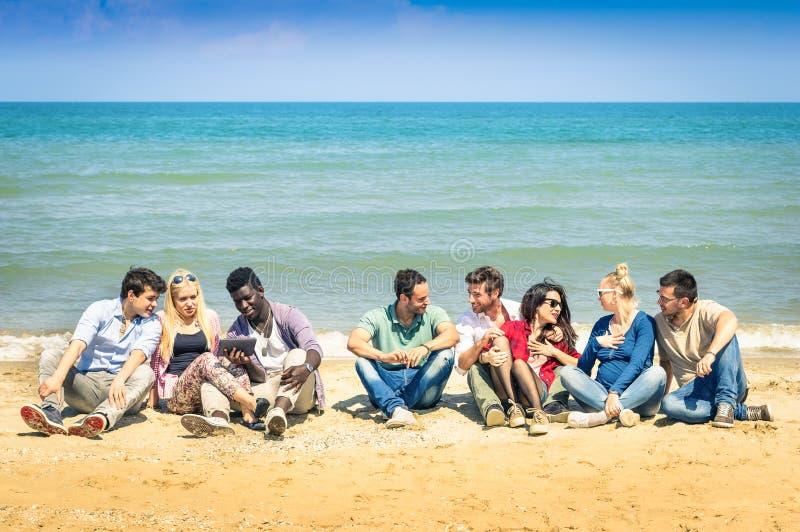 Groep multiraciale beste vrienden die bij strand spreken stock afbeeldingen