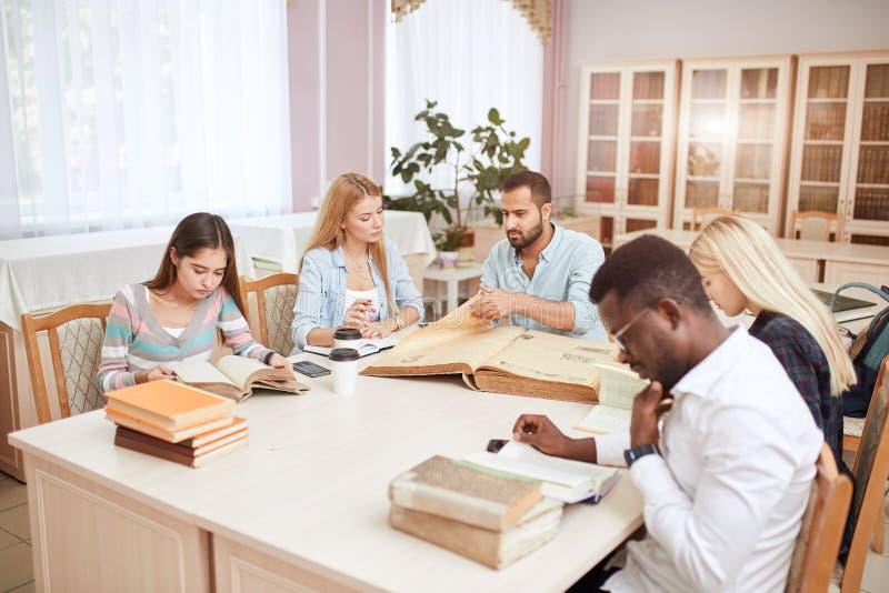Groep multiraciale mensen die met boeken in universiteitsbibliotheek bestuderen royalty-vrije stock fotografie