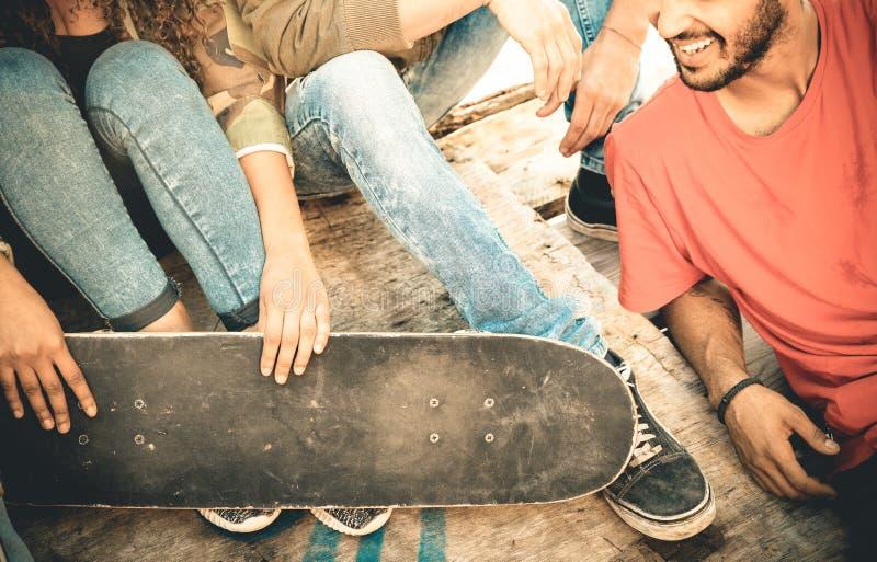 Groep multiraciale vrienden die pret hebben bij skateboardpark stock afbeelding