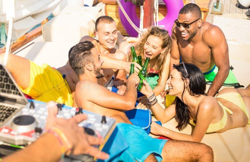 Groep multiraciale vrienden die pret het drinken hebben bij de partij van de zeilboot stock afbeelding