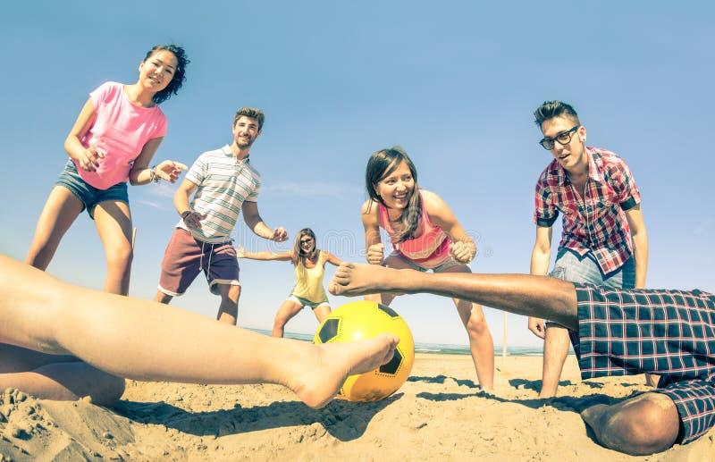Groep multiraciale vrienden die strandvoetbal spelen bij de zomer stock afbeelding