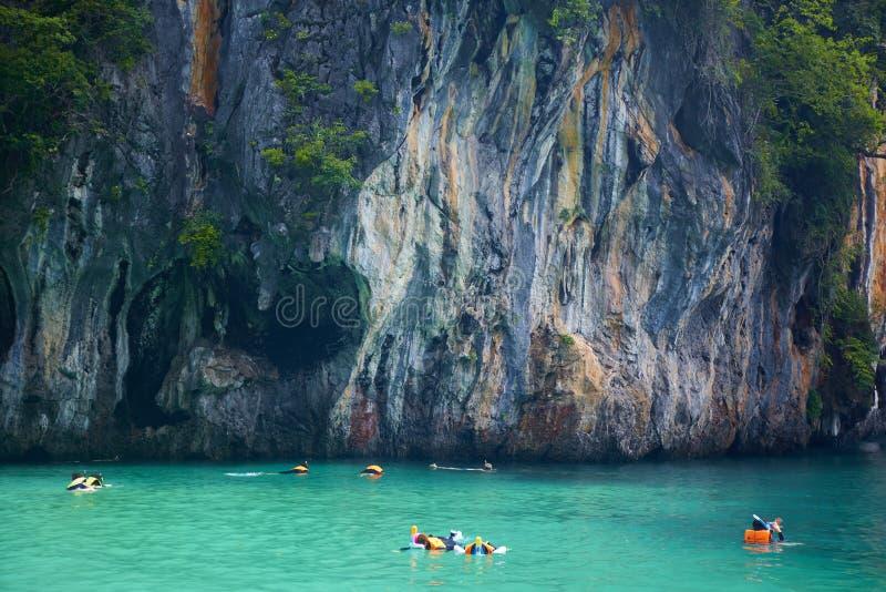 Groep niet geïdentificeerde mensen die in paradijslagune zwemmen royalty-vrije stock afbeelding