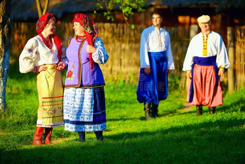 Groep Oekraïense mensen die het dorp na volksfestiviteiten lopen stock fotografie