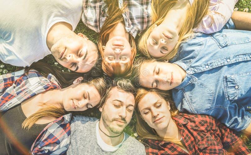 Groep onbezorgde beste vrienden die samen op grasweide ontspannen stock foto