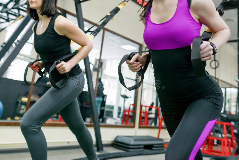 Groep opleiding met geschiktheidslijnen in de gymnastiek, twee jonge aantrekkelijke atletenvrouwen die crossfit met riemensysteem royalty-vrije stock foto