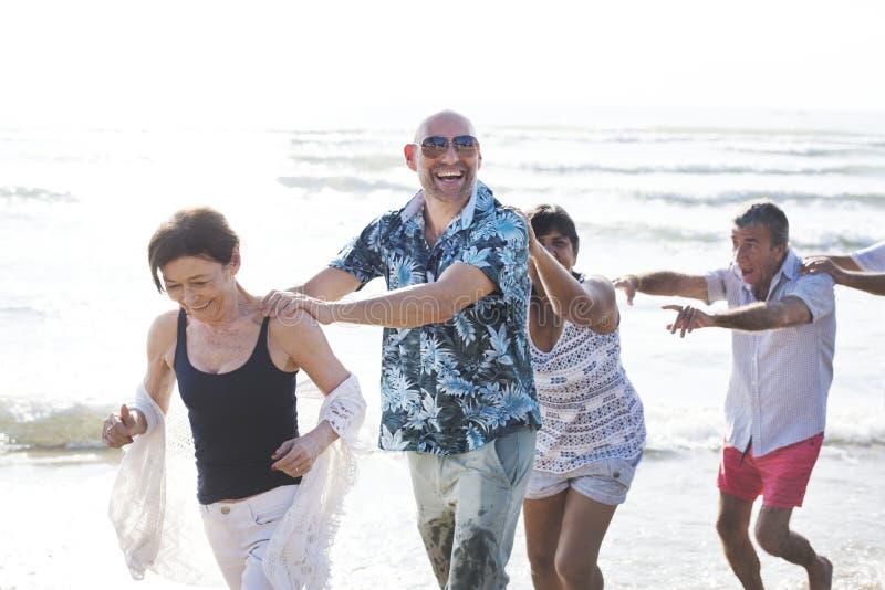 Groep oudsten op het strand stock afbeeldingen
