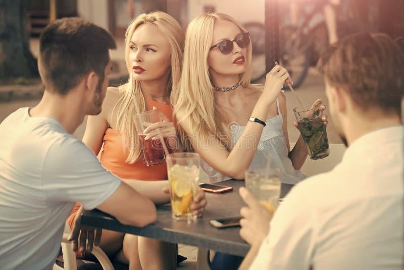 Groep partijmensen, twee paren met cocktails in bar royalty-vrije stock fotografie