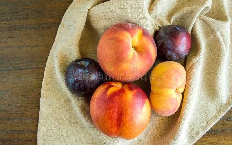 Groep perziken en pruimen op een beige servet stock afbeelding