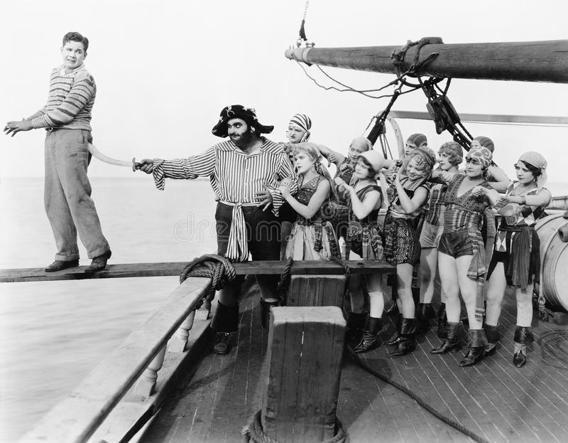 Groep piraten die een jonge mens over een plank proberen te duwen (Alle afgeschilderde personen leven niet langer en geen landgoe royalty-vrije stock fotografie