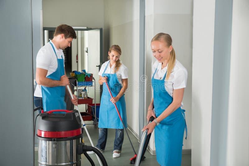 Groep Portiers die Vloer in Gang schoonmaken stock afbeeldingen