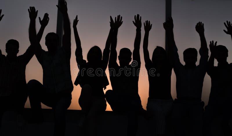 Groep positieve jongeren die op een vensterbank zitten stock foto's
