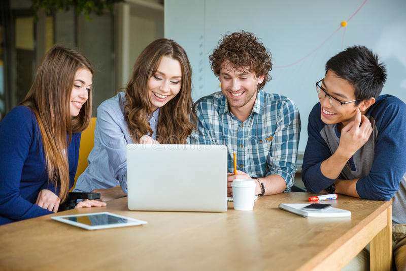 Groep positieve vrolijke studenten die thuiswerk samen in klaslokaal doen stock fotografie