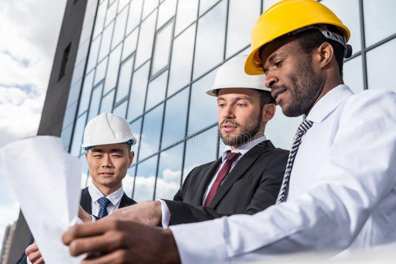 Groep professionele architecten in helmen die met blauwdruk buiten de moderne bouw werken royalty-vrije stock fotografie