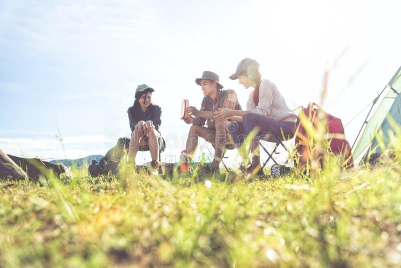 Groep reizigers die en picknick in het voorste gedeelte van het weidegebied kamperen doen royalty-vrije stock foto's