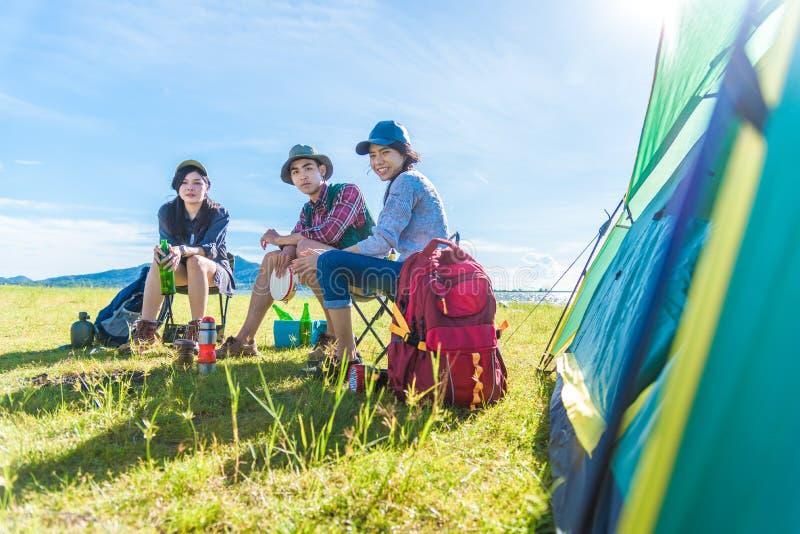 Groep reizigers die en picknick in weide met tent doen kamperen royalty-vrije stock foto