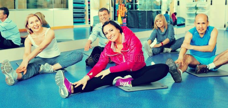 Groep rijpe mensen die op sportmatten uitoefenen stock afbeeldingen