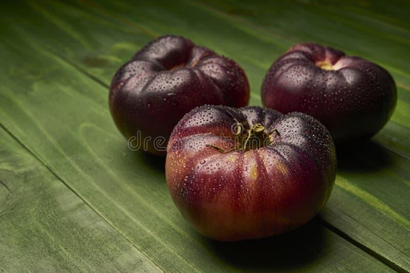 Groep rijpe R.A.F.-tomaten op groene houten achtergrond stock foto's