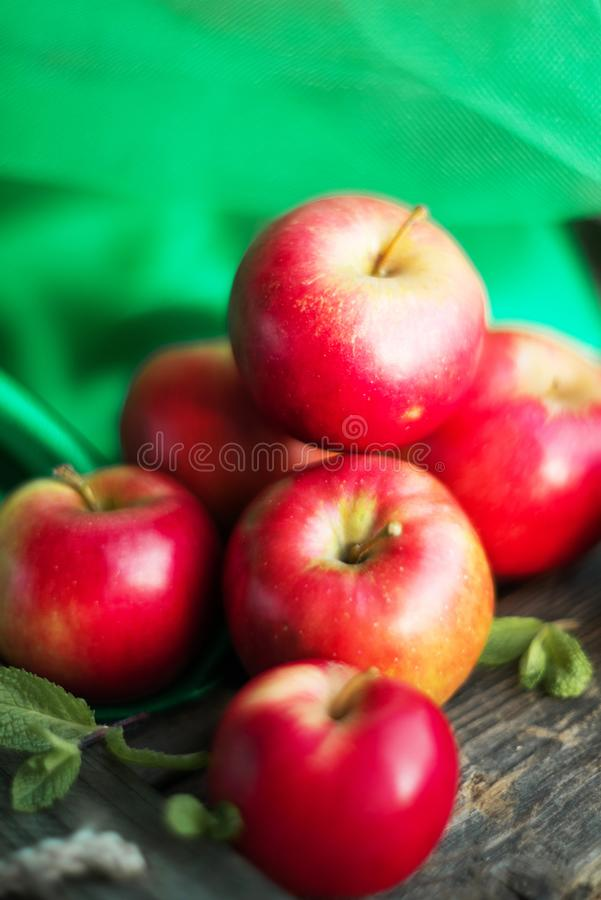 groep rode appelen op houten natuurlijke achtergrond, vers natuurvoeding en vitaminenconcept in rustieke stijl royalty-vrije stock afbeeldingen